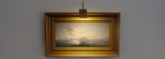 een tradionele schilderijverlichting boven het werk